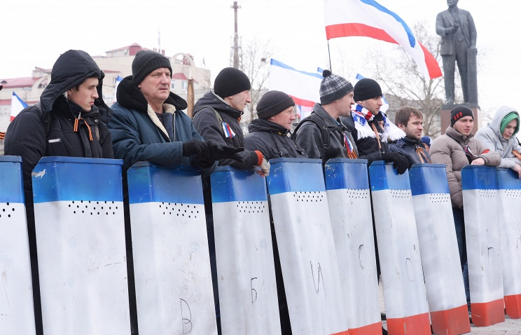 A self defense unit in Crimea carries shields with the colours of the Crimean flag